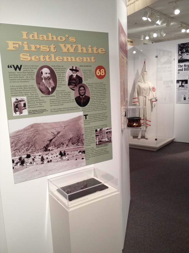 "Panel describing ""Idaho's First White Settlement"" is placed adjacent to an exhibit of a Ku Klux Klan costume."